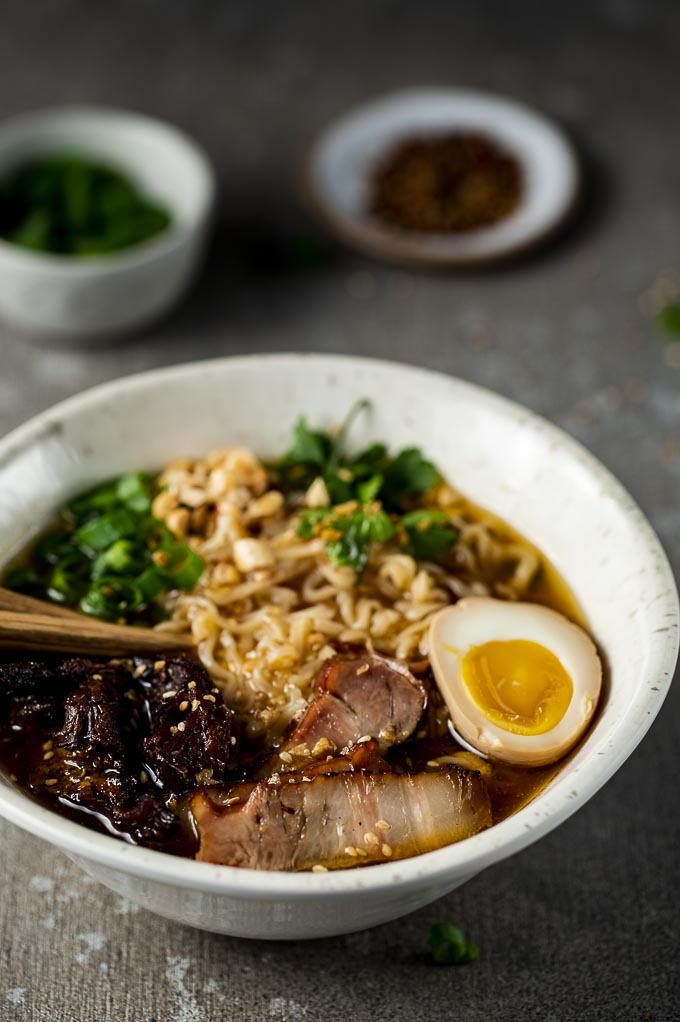 pork ramen in a bowl with a soft boiled egg, green onions, noodles and a spoon