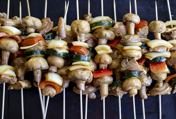raw chicken and vegetables on skewers