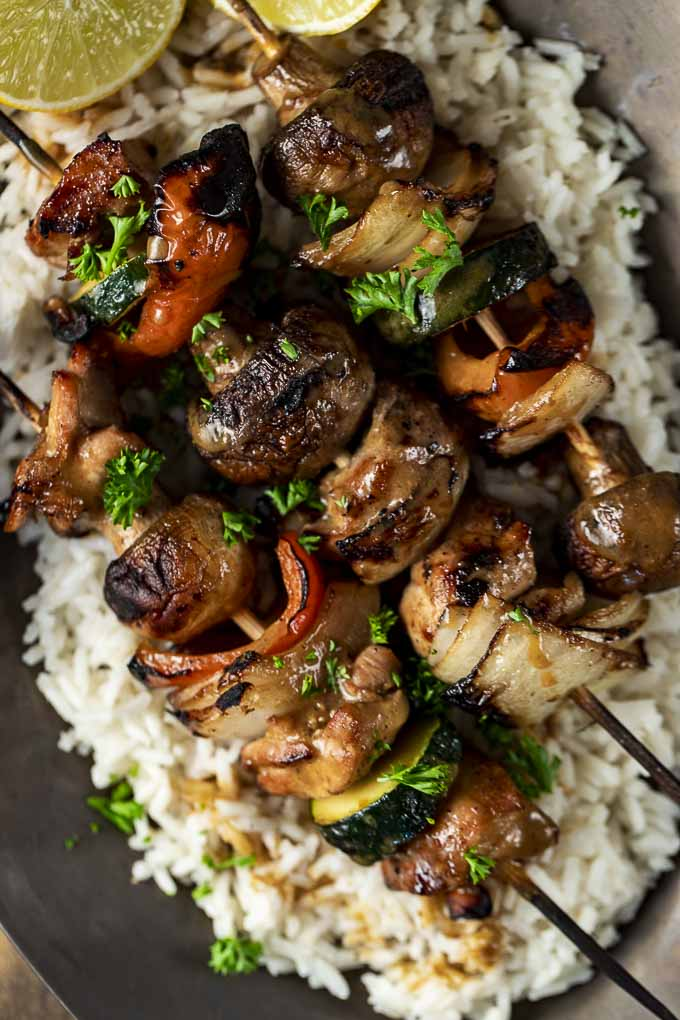 chicken skewers with vegetables on a bed of rice