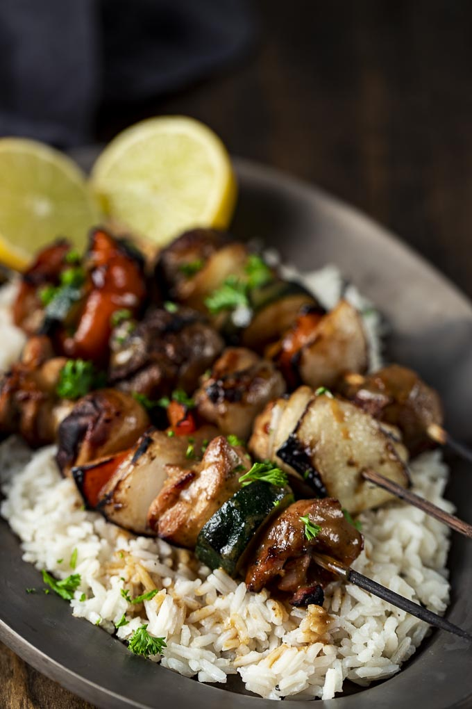 skewers of cooked chicken and veggies on a plate