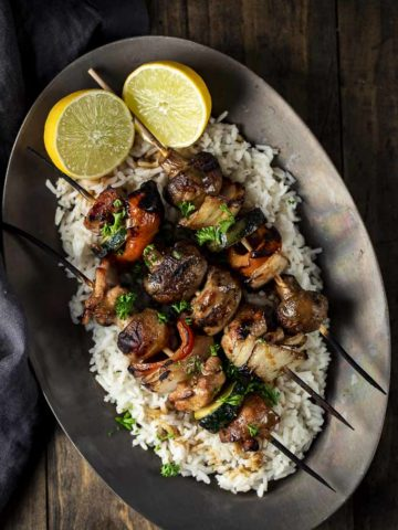 chicken kabobs on a plate with rice