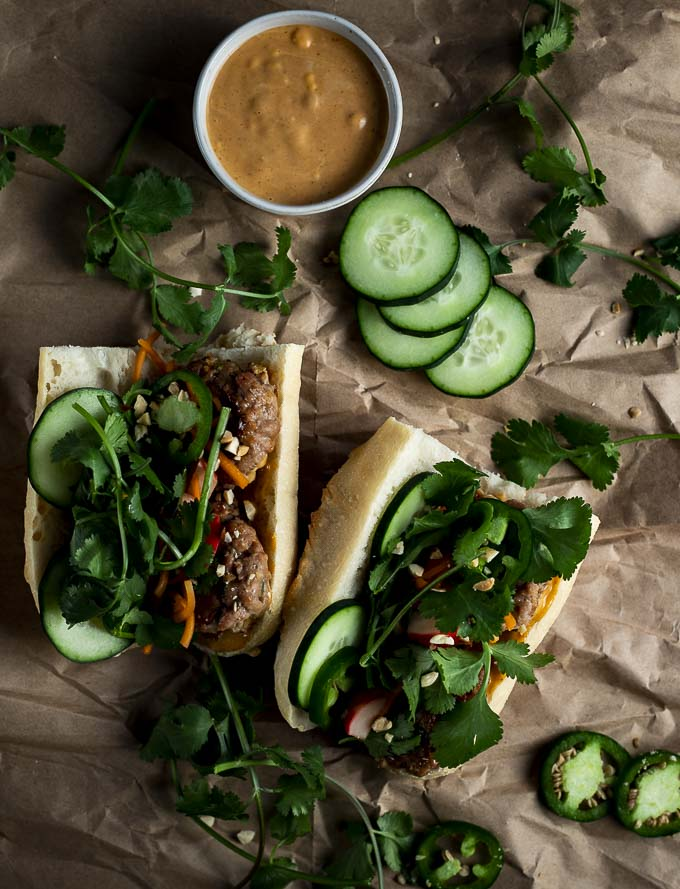 banh mi sandwiches on paper with meatballs, vegetables, fresh herbs and sauce on the side