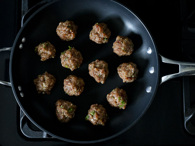 raw meatballs in a skillet