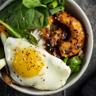 rice bowl topped with egg, vegetables and shrimp