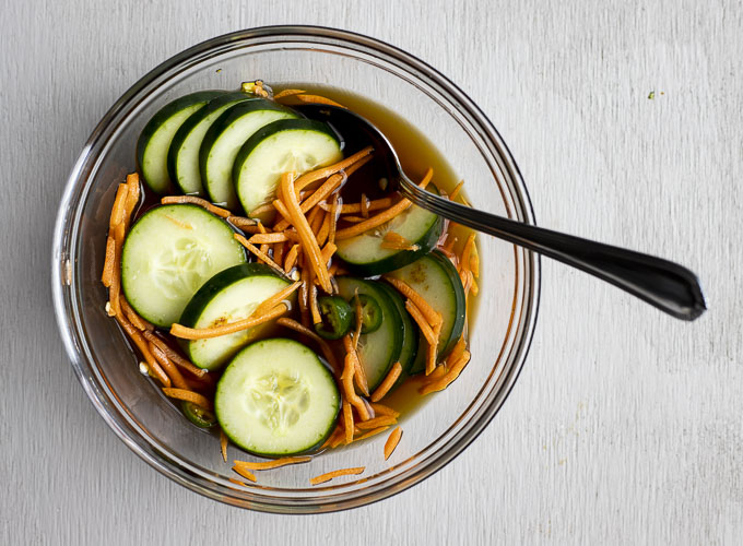 cucumber and carrots in a bowl with brown liquid