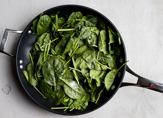 raw spinach in a skillet with salt