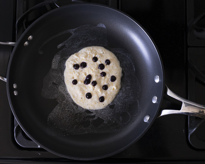 pancake batter with blueberries in a skillet