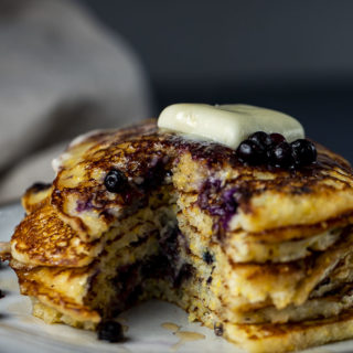 stack of pancakes cut open with butter and blueberries on top