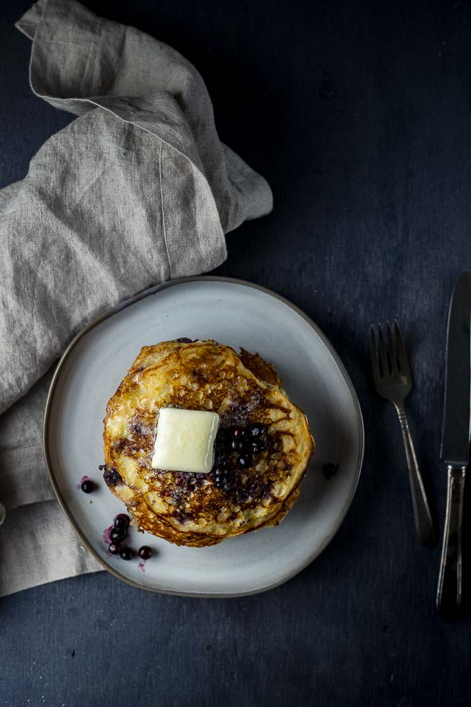 pancakes on a plate topped with butter and blueberries