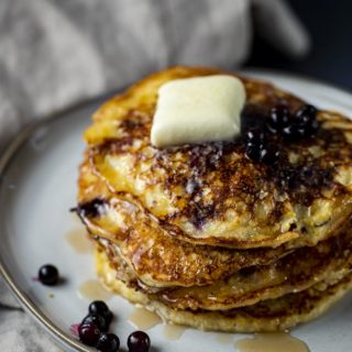 blueberry pancakes on a plate with blueberries on top