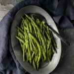 green beans on a platter with a spoon