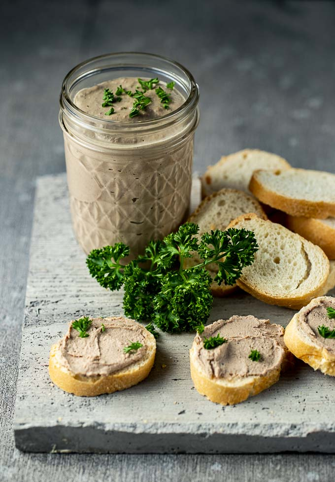 jar of chicken liver mousse with some spread on pieces of bread