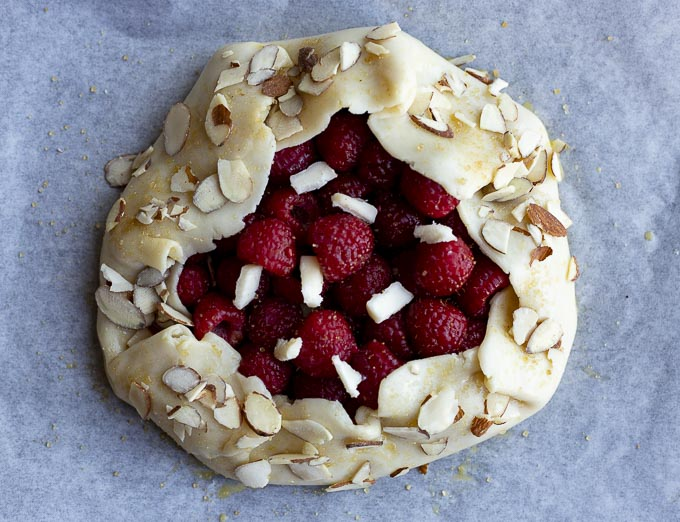 raspberries in a pie crust topped with almonds and cold butter