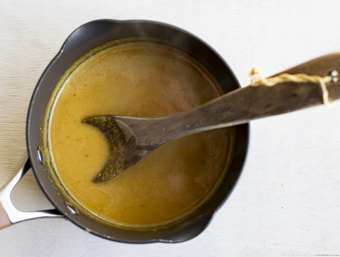an orange colored sauce in a saucpan