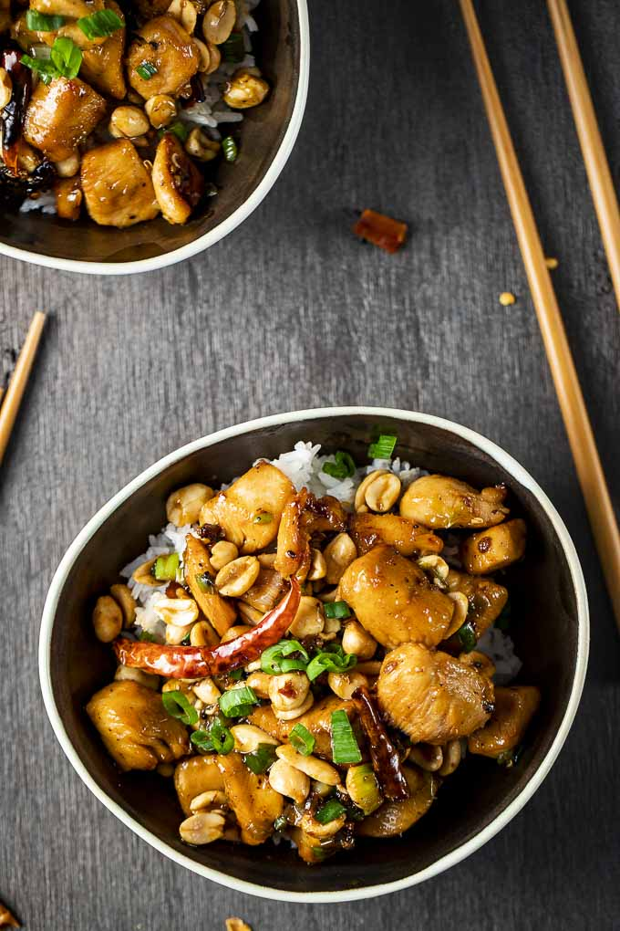 bowl of chicken and chilies with peanuts over rice