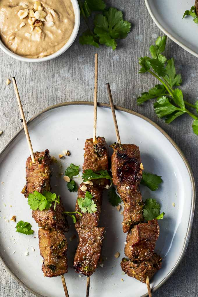 3 skewers of beef on a plate with cilantro