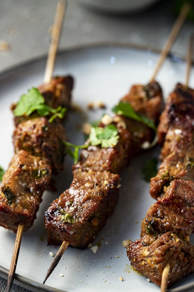 beef skewers on a plate garnished with cilantro