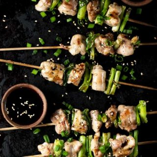 yakitori on a platter with sauce bowls and sesame seeds