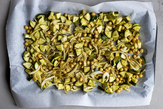 diced zucchini and chickpeas with seasoning on a baking sheet