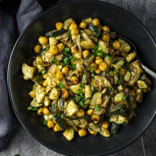 bowl of roasted zucchini and chickpeas garnished with green onions
