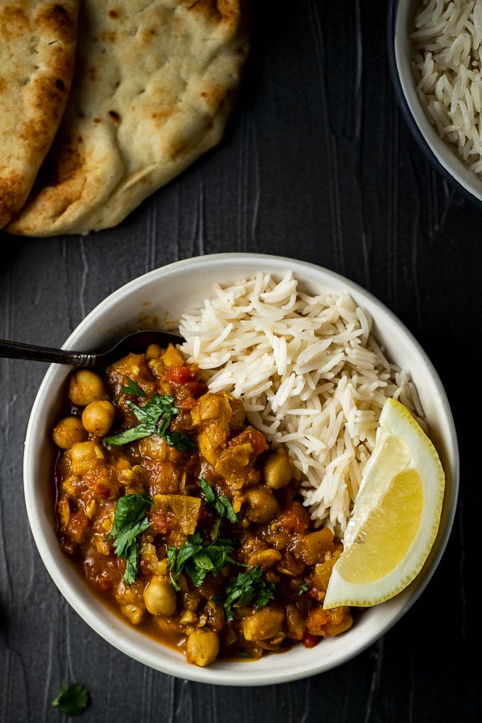 bowls of chana masala garnished with cilantro and naan on the side