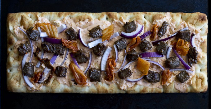 beef, onions and kimchi with sauce on pizza crust