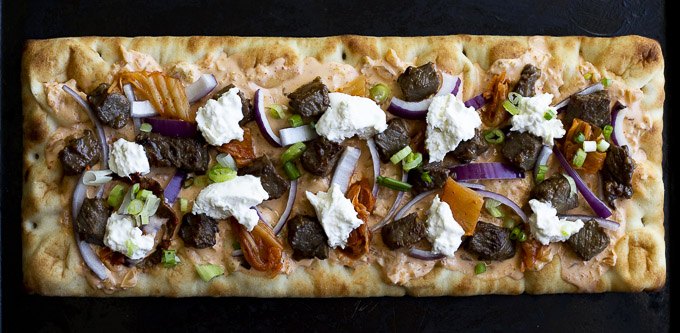 uncooked pizza topped with beef onions, and burrata cheese
