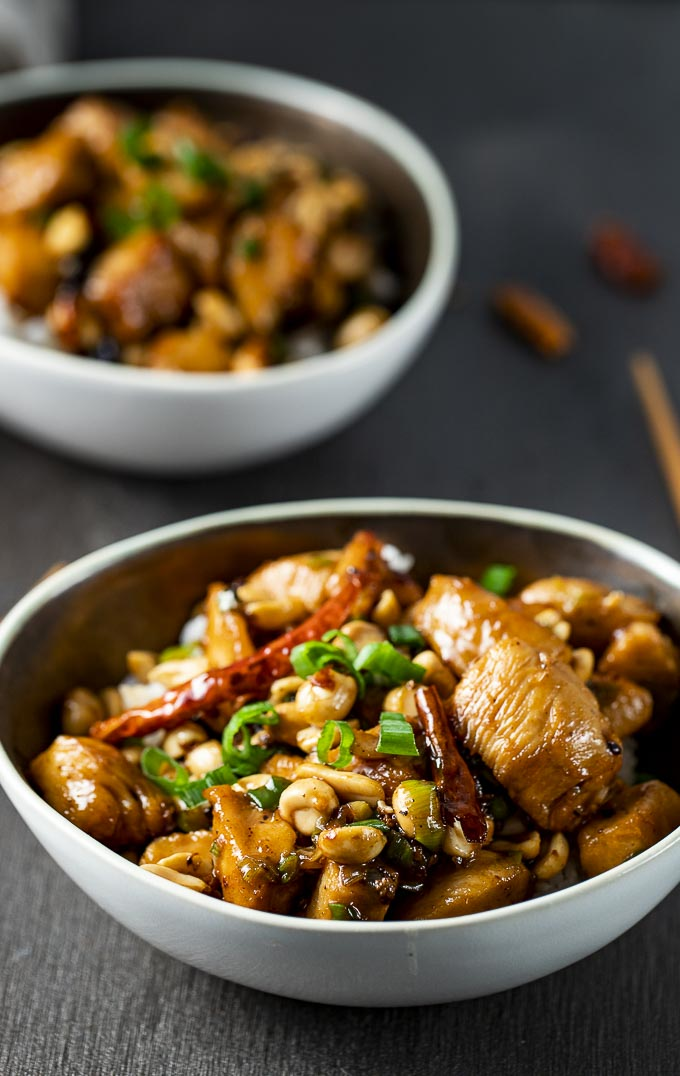bowl of stir fried chicken with peanuts ad chilies in orange sauce