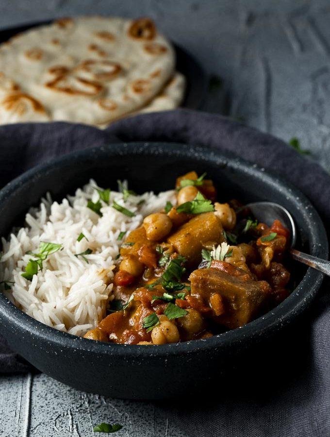 a bowl of curry with a spoon and naan bread on the side