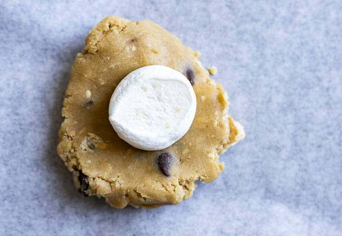 half a marshmallow on top of a piece of raw cookie dough