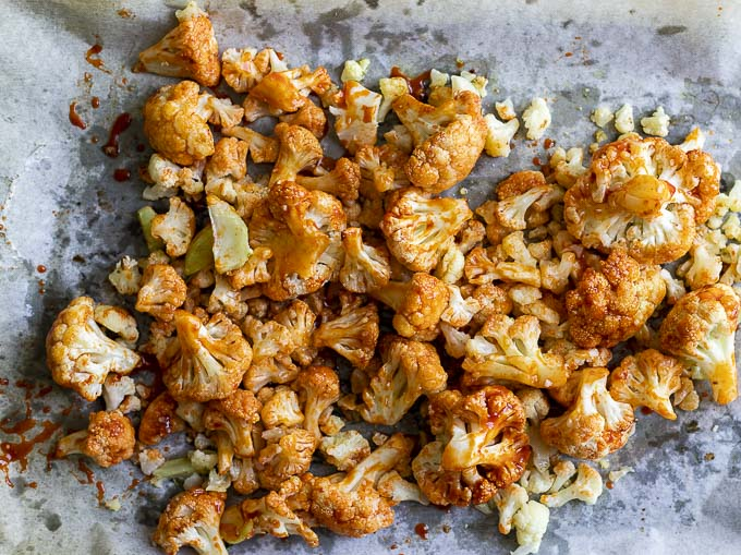 cauliflower on a baking sheet covered in orange sauce