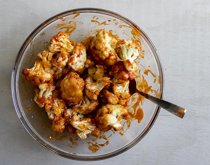 cauliflower in a bowl covered in orange sauce