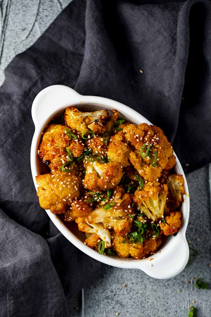 cauliflower in orange sauce in a dish with sesame seeds