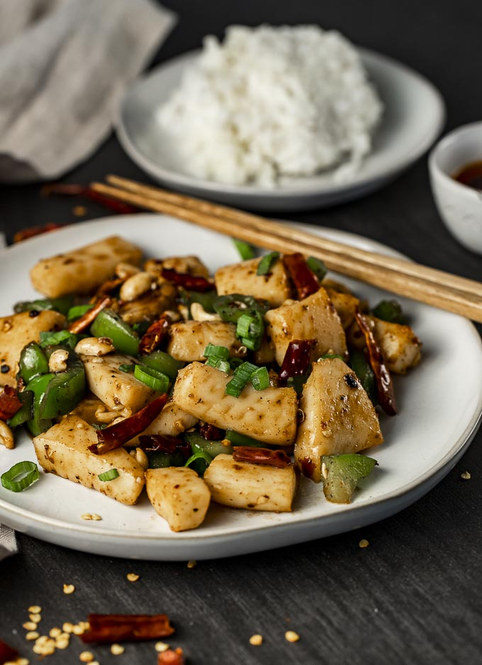 kung pao calamari on a plate with chopsticks and green onions