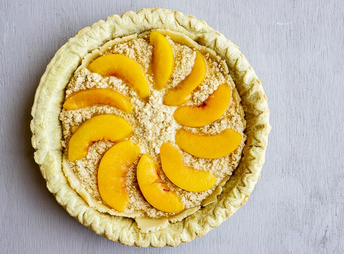 batter in pie crust with sliced peaches on top