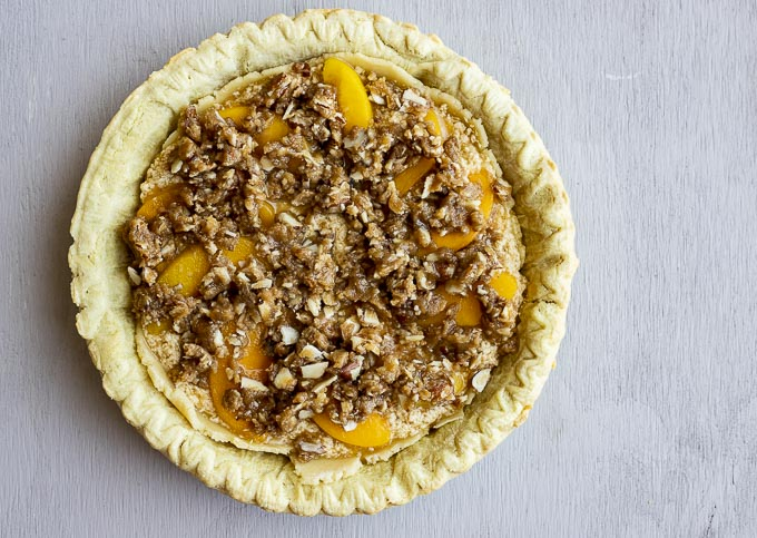 unbaked pie topped with peaches and struesel topping
