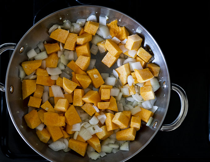 cubes of butternut squash and onions in a skillet