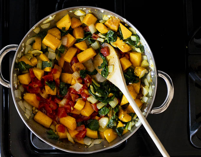 tomatoes, butternut squash and spinach in a skillet