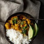 a bowl of orange butternut squash curry with rice and sliced limes