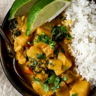 orange colored butternut squash curry in a bowl with rice and fresh lime slices