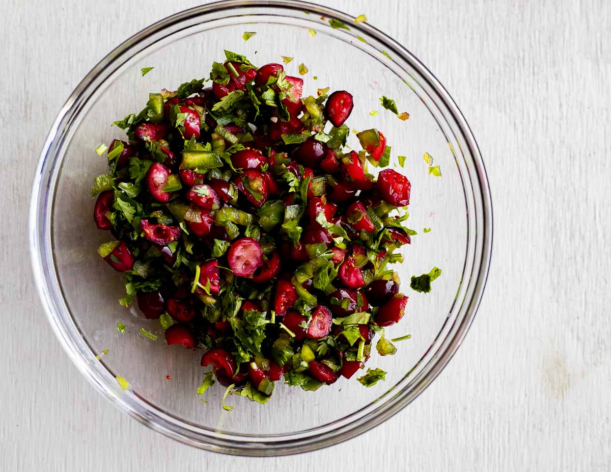cranberries, jalapenos and cilantrol mixed together in a glass bowl
