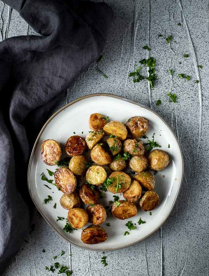 roasted mini potatoes on a plate garnished with parsley
