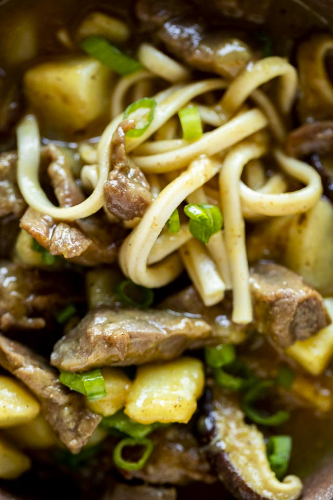 noodles, beef, mushrooms and vegetables in a brown curry sauce