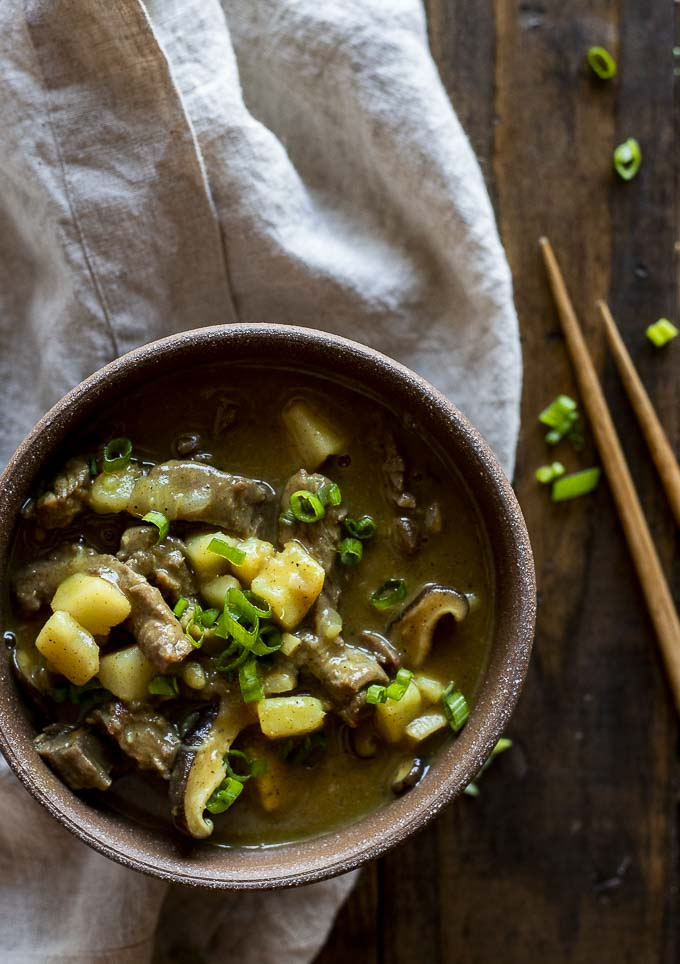 beef, potatoes and mushrooms in a bowl of brown sauce sprinkled with green onions