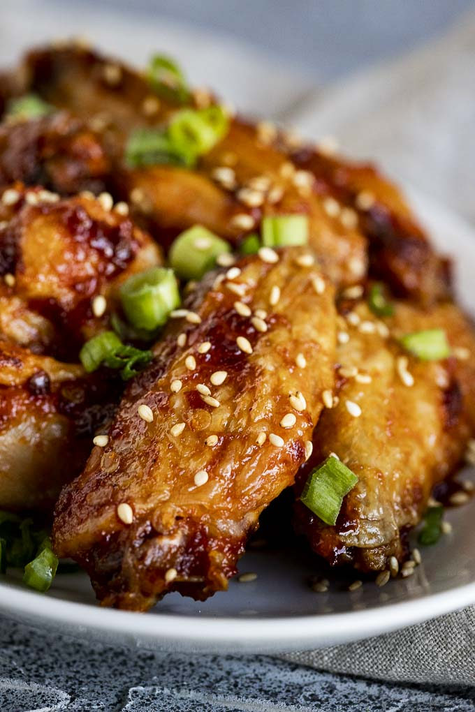 chicken wings in an orange sauce sprinkled with sesame seeds and green onions