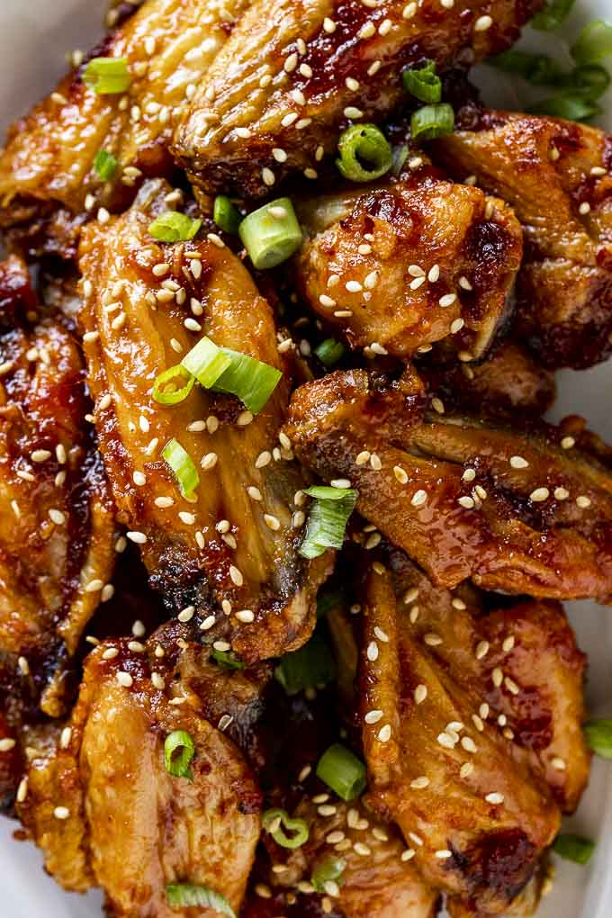 chicken wings in an orange glaze with green onion slices and sesame seeds on top