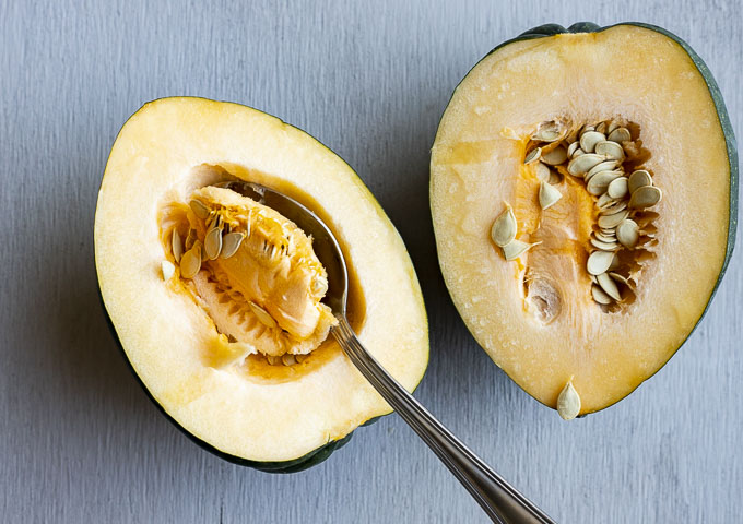 a spoon scooping out the seeds of half an acorn squash