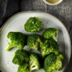 broccoli on a plate with lemon butter on the side