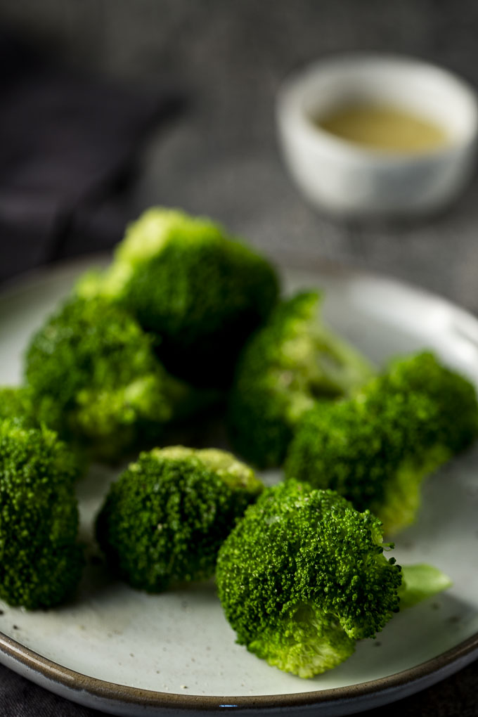 cooked broccoli on a plate with bowl of liquid in the back