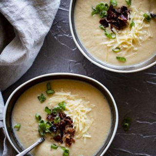 pureed cauliflower soup in bowls with spoons, bacon, green onions and shredded cheese